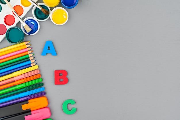 Lápices de colores, marcadores y pinturas sobre un pupitre gris