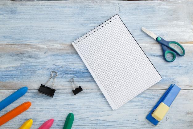 Lápices de colores o crayones, tijeras, grapadora y bloc de notas en madera vintage azul y blanco, vista superior