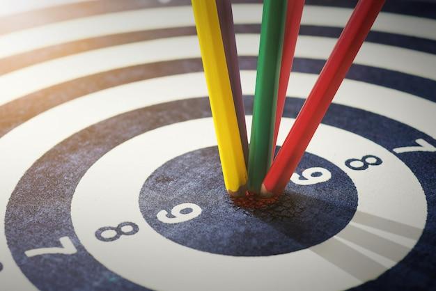 Lápices de colores en el ojo de buey éxito que golpea objetivo objetivo objetivo logro concepto fondo