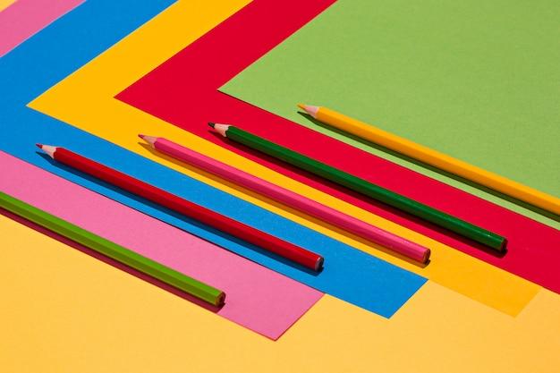 Lápices de colores y papel de color.