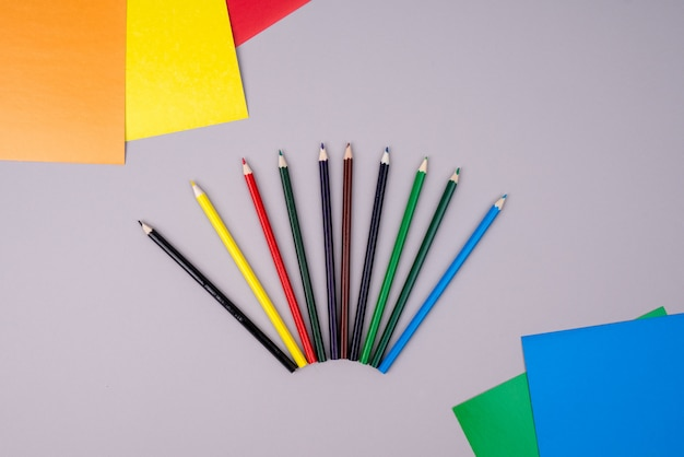 Lápices de colores y papel de colores sobre gris.