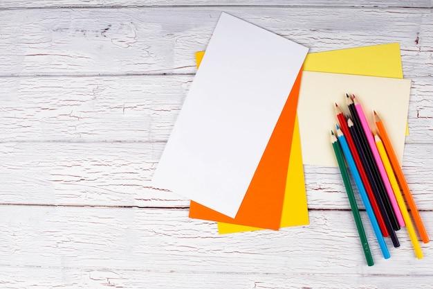 Los lápices de colores y papeles se colocan sobre la mesa