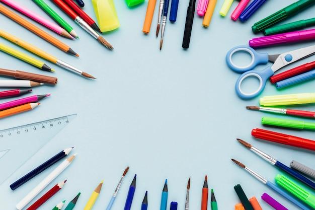 Lápices de colores y pinceles en forma de marco.
