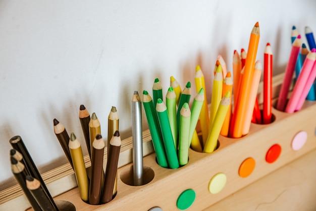 Lápices de colores en un recipiente en una mesa de madera, de cerca en verdes