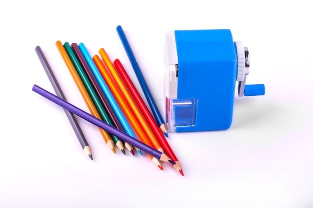 Lápices de colores y sacapuntas mecánico sobre fondo blanco.