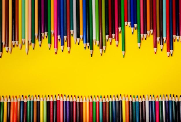 Lápices de colores sobre fondo amarillo. papelería sobre papel. marco de útiles escolares de oficina