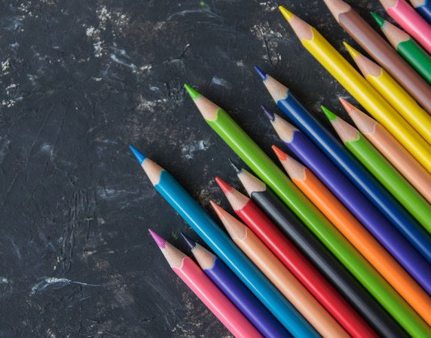 Lápices de colores sobre el fondo estructural natural. de cerca.