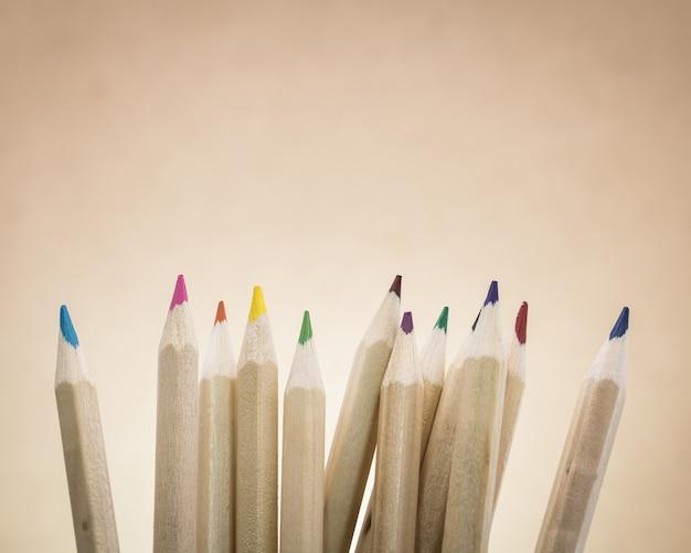 Lápices de colores sobre fondo marrón. un grupo de lápices de madera de color.
