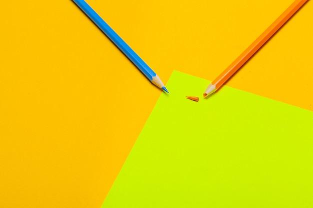 Lápices de colores sobre un fondo de papel verde brillante