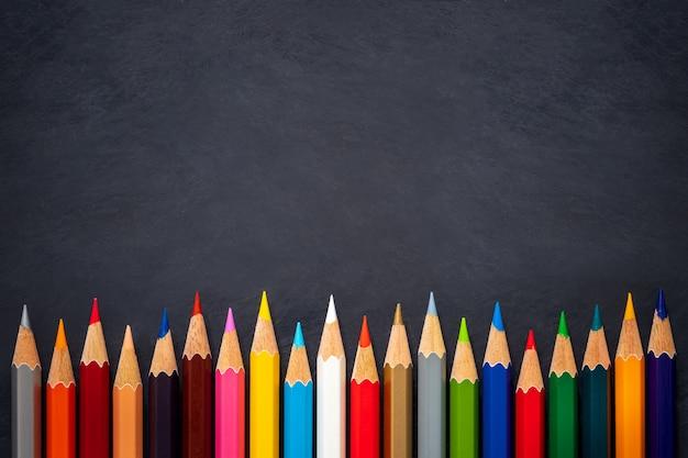 Lápices de colores sobre fondo de pizarra
