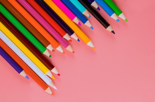 Lápices de colores sobre fondo rosa para arte y escuela