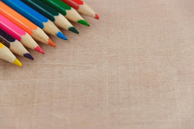 Lápices de colores sobre fondo de textura de madera