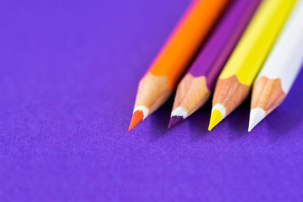 Lápices de colores sobre un fondo violeta con espacio para texto.