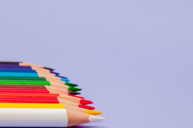 Lápices de colores sobre fondo violeta para proyectos y anuncios