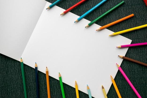 Lápices de colores sobre papel blanco copia espacio sobre madera