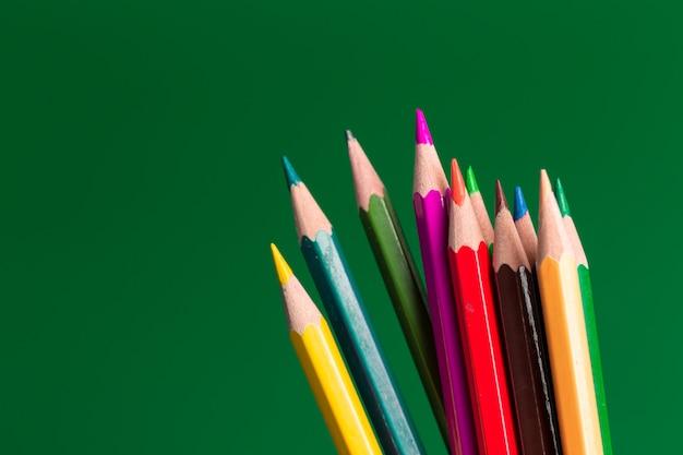 Lápices de colores sobre papel verde