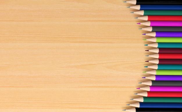 Lápices de colores sobre tabla de madera para el fondo, representación 3d