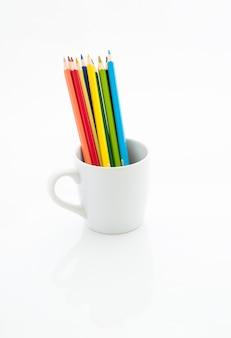 Lápices de colores en taza de café blanco