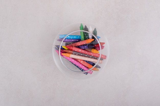 Lápices de colores en vidrio sobre fondo blanco.