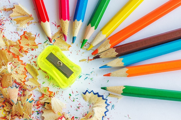 Lápices de colores, virutas de lápices y un sacapuntas.