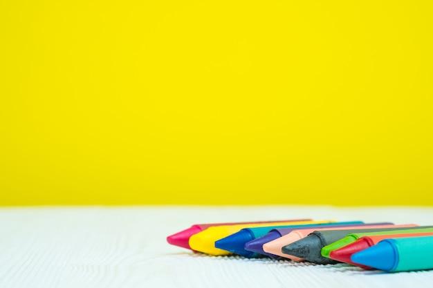 Lápices coloridos de los creyones de cera en la tabla de madera blanca con el espacio de la copia.