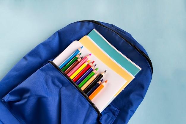 Lápices y cuadernos de madera multicolores en una mochila sobre un fondo de papel azul con espacio de copia. accesorios escolares.