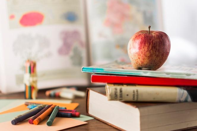 Lápices de colores cerca de libros y manzana