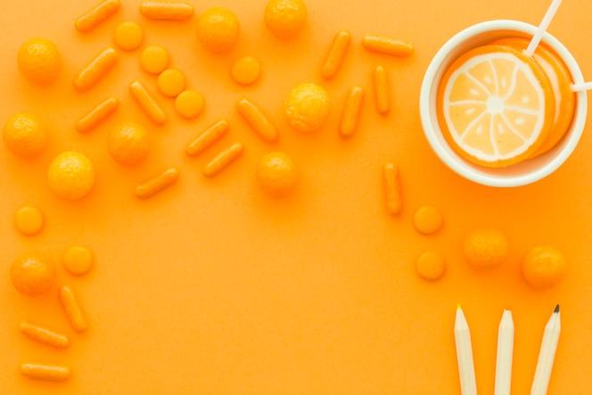 Lápices de colores cerca de piruletas y dulces sobre fondo naranja