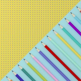 Lápices de colores sobre fondo de contraste de patrón de punto de color azul y amarillo.