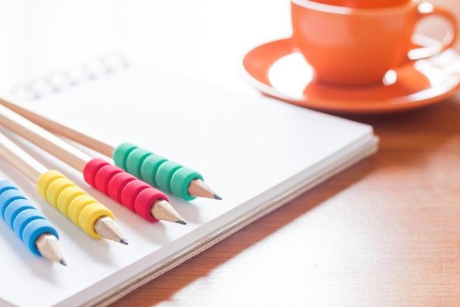 Lápices en el cuaderno blanco en blanco abierto con taza de café en el escritorio