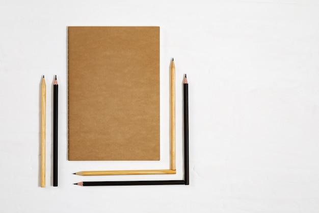 Lápices geométricos doblado y cerrado cuaderno sobre escritorio blanco. seis lápices de madera y un libro para dibujar. concepto de regreso a la escuela. copia espacio vista superior.