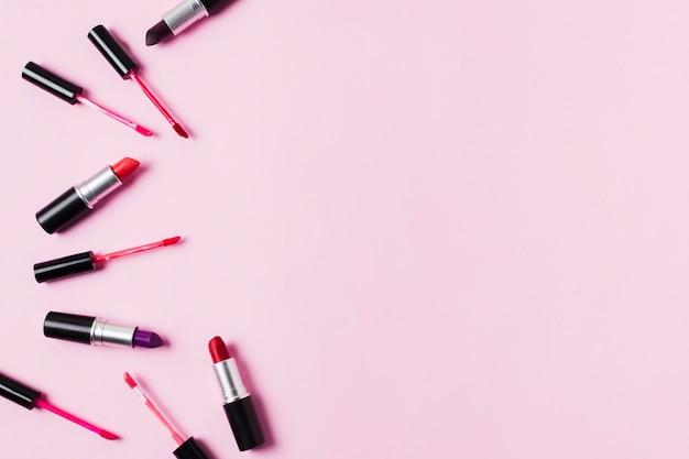 Lápices labiales y brillos de labios esparcidos sobre fondo rosa
