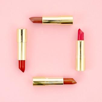 Lápices labiales de colores sobre fondo rosa