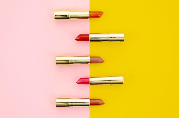 Lápices labiales de diferentes colores sobre fondo rosa y amarillo