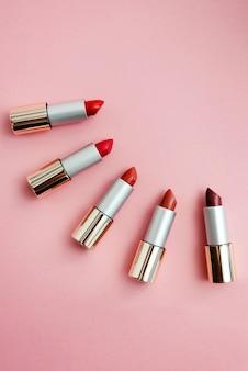 Lápices labiales en diferentes tonos de rosa y rojo. copyspace, vista superior