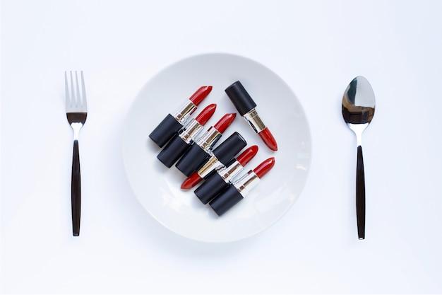 Lápices labiales en plato blanco con tenedor y cuchara en blanco