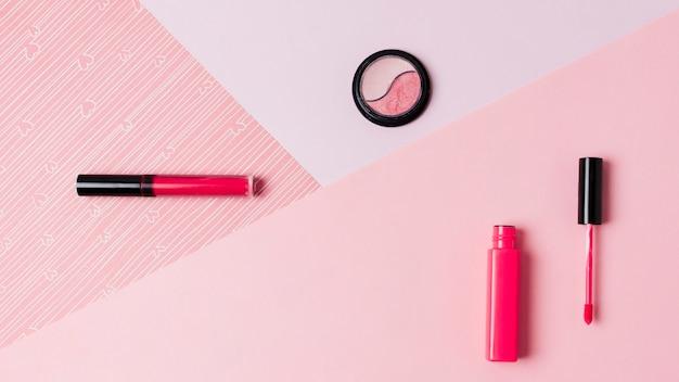 Lápices labiales y sombra de ojos sobre superficie clara.
