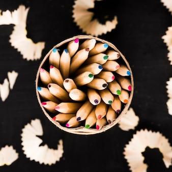 Lápices en lata y virutas sobre fondo negro
