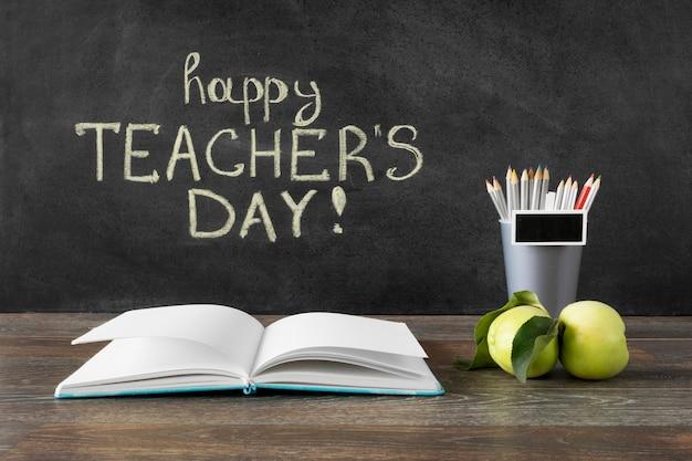 Lápices y libro concepto feliz del día del maestro.