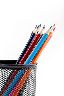 Lápices multicolores para pintar y dibujar dentro de una pequeña canasta negra en la pared blanca