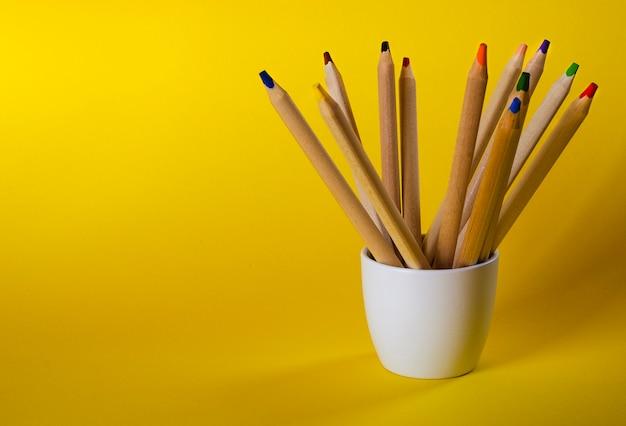 Lápices multicolores sobre amarillo