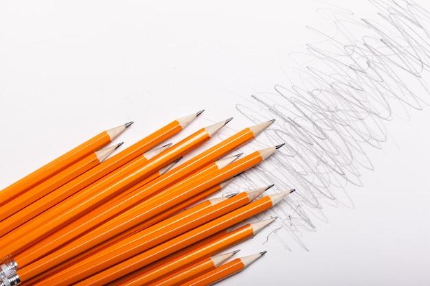 Lápices naranjas cerca aislado en blanco