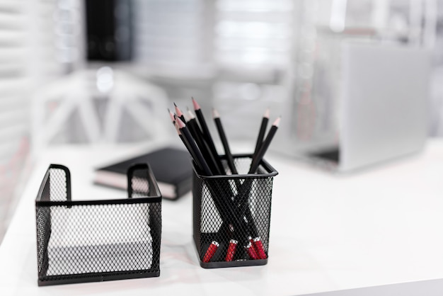 Lápices negros en una caja sobre la mesa blanca.