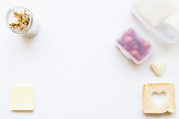 Lápices y notas adhesivas cerca de la comida del almuerzo