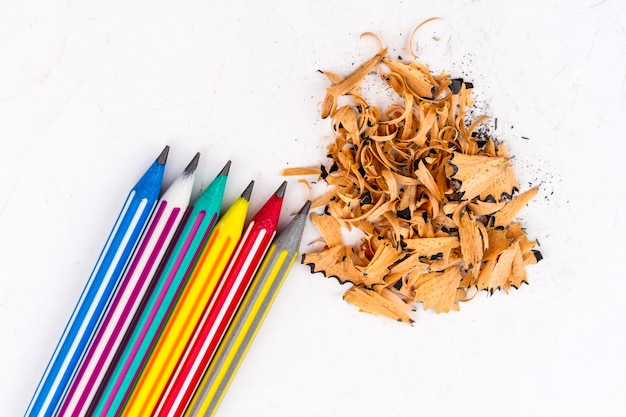 Lápices del penique y lápiz colorido en un fondo blanco.