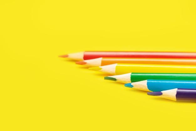 Lápices que hacen la bandera lgbt aislada sobre fondo amarillo