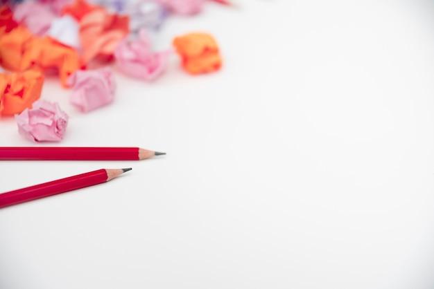 Lápices rojos afilados y papel arrugado sobre fondo blanco