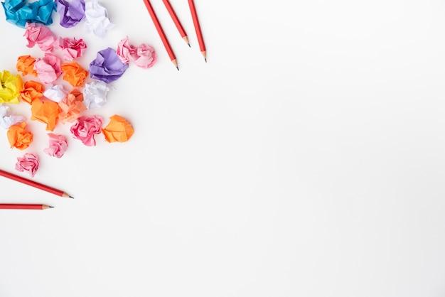 Lápices rojos y papel arrugado de colores sobre superficie blanca