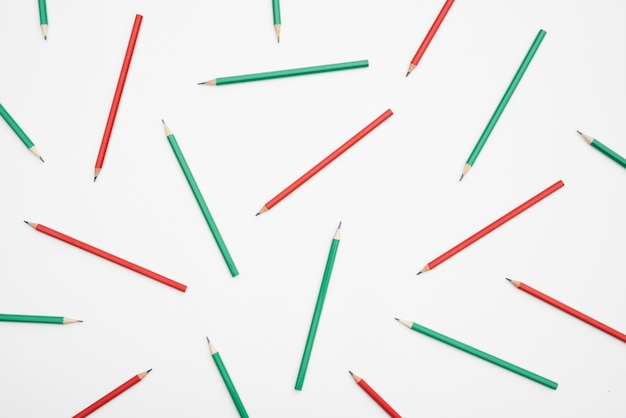 Lápices rojos y verdes sobre fondo blanco.