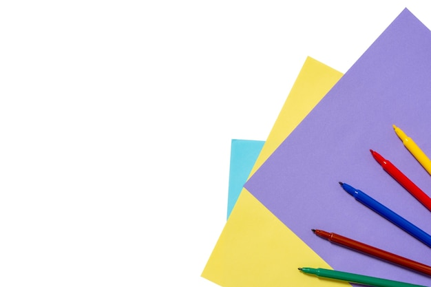 Lápices, rotuladores de colores del arco iris en hojas de papel azul, amarillo, lila aislado sobre un fondo blanco.